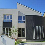 Rの外壁が印象的。ホワイトとブラウンで家全体に安心感や安定感、温もりをイメージしています。