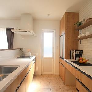 床をタイル張りにしたキッチン。汚れも簡単に拭き取れて床汚れは気になりません。カップボード・棚は収納豊富で、可愛らしさも引き立てます。