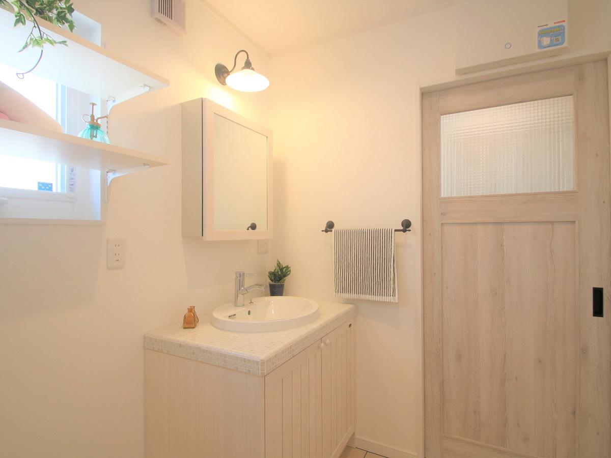 可愛らしい洗面化粧台と洗面室入り口ドア。窓上に収納棚がスペースを有効活用します。