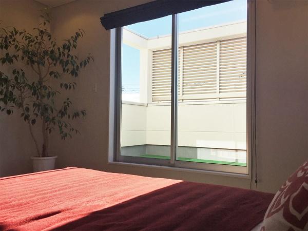ベッドルームにつながる大きなバルコニーは夫婦だけのセカンドリビング。目隠しの格子が外部からの視線も遮ります。