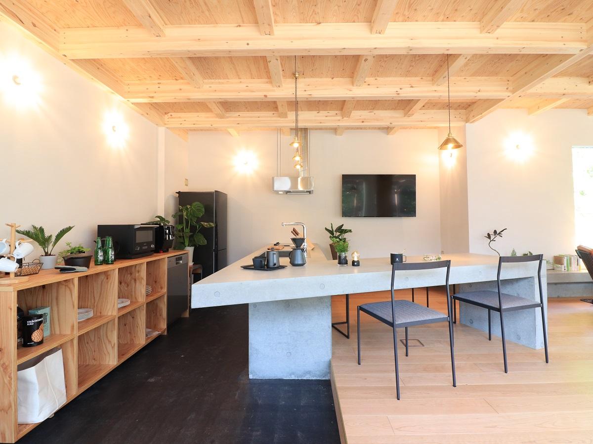 コンリートキッチンのカウンターがダイニングテーブルまで繋がり、空間にダイナミックな印象を与えています。