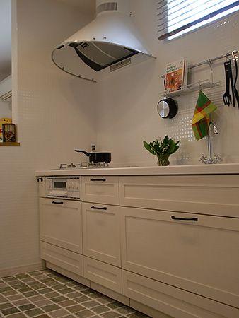 無垢素材のシステムキッチンとモザイクタイルに囲まれたアンティーク調のマウントフード。