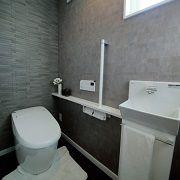 トイレはリビングからの死角の場所に設け、壁の一部にタイルを施しシックにまとめました。