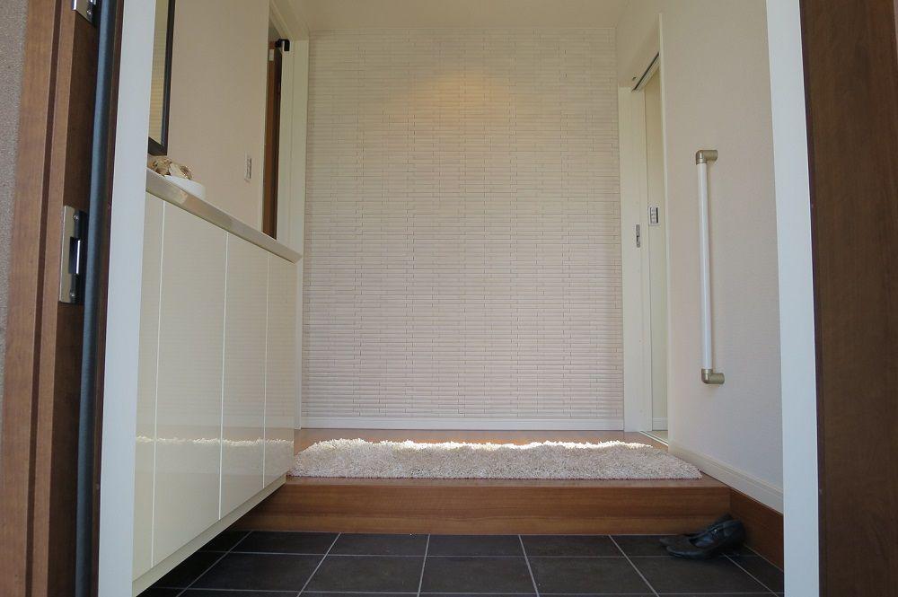 玄関を開けると、正面の壁にはエコカラット(内装壁材)を採用。玄関にアクセントを持たせるだけでなく、湿度を調整したり消臭したりと優れた性能を発揮します。