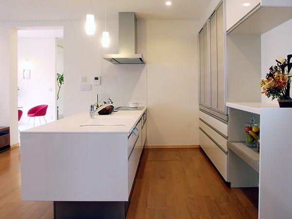 収納は背面の壁面一面にカップボードを配して、吊戸棚をなくして空間にもゆとりをプラス。