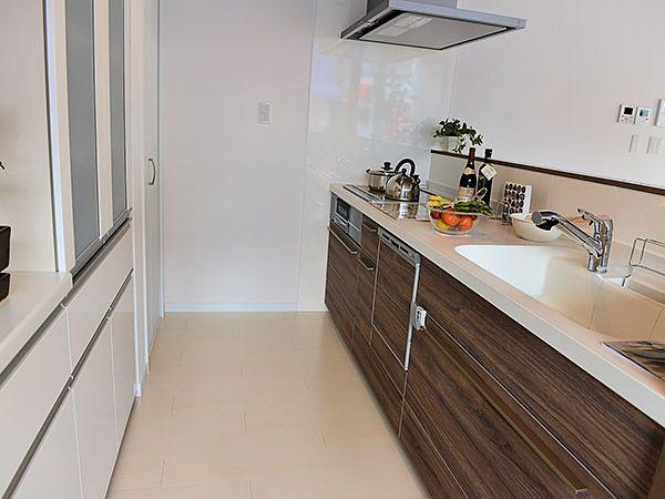 カウンター、天井の板張りと同色の、木の温かみある扉。キッチン前カウンターは、上部は開放的にし手元はしっかり隠れる高さにしました