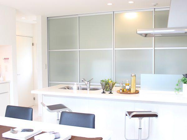キッチン後ろは冷蔵庫も入る大容量収納。来客時はアクリル扉で楽々と隠せます。