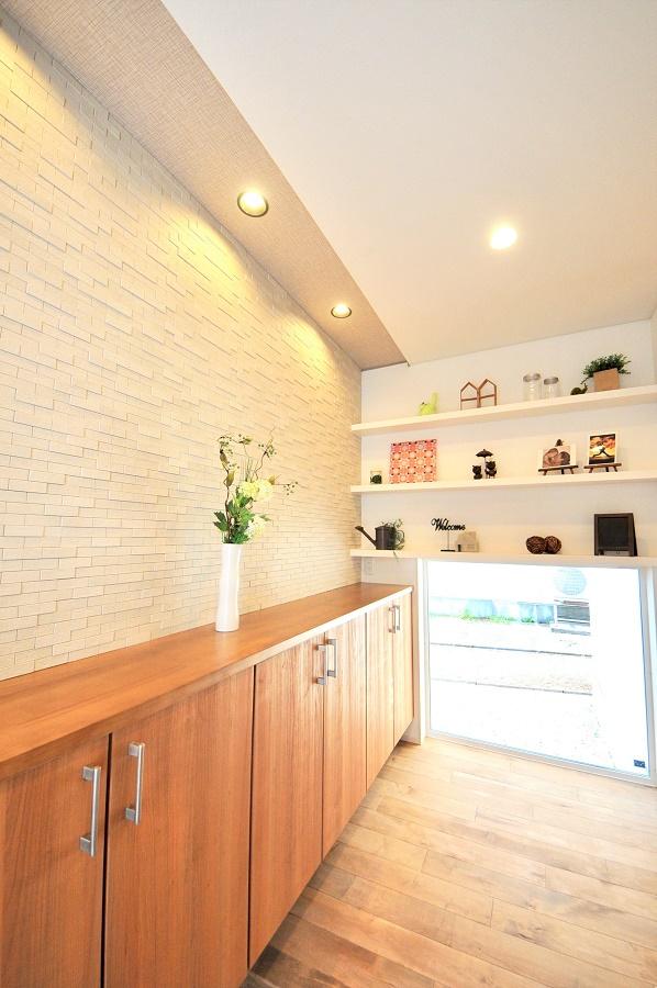 大きな玄関収納と正面の壁面ディスプレイが特徴。クローク上はタイルで玄関廻りの湿気対策に効果を発揮する。