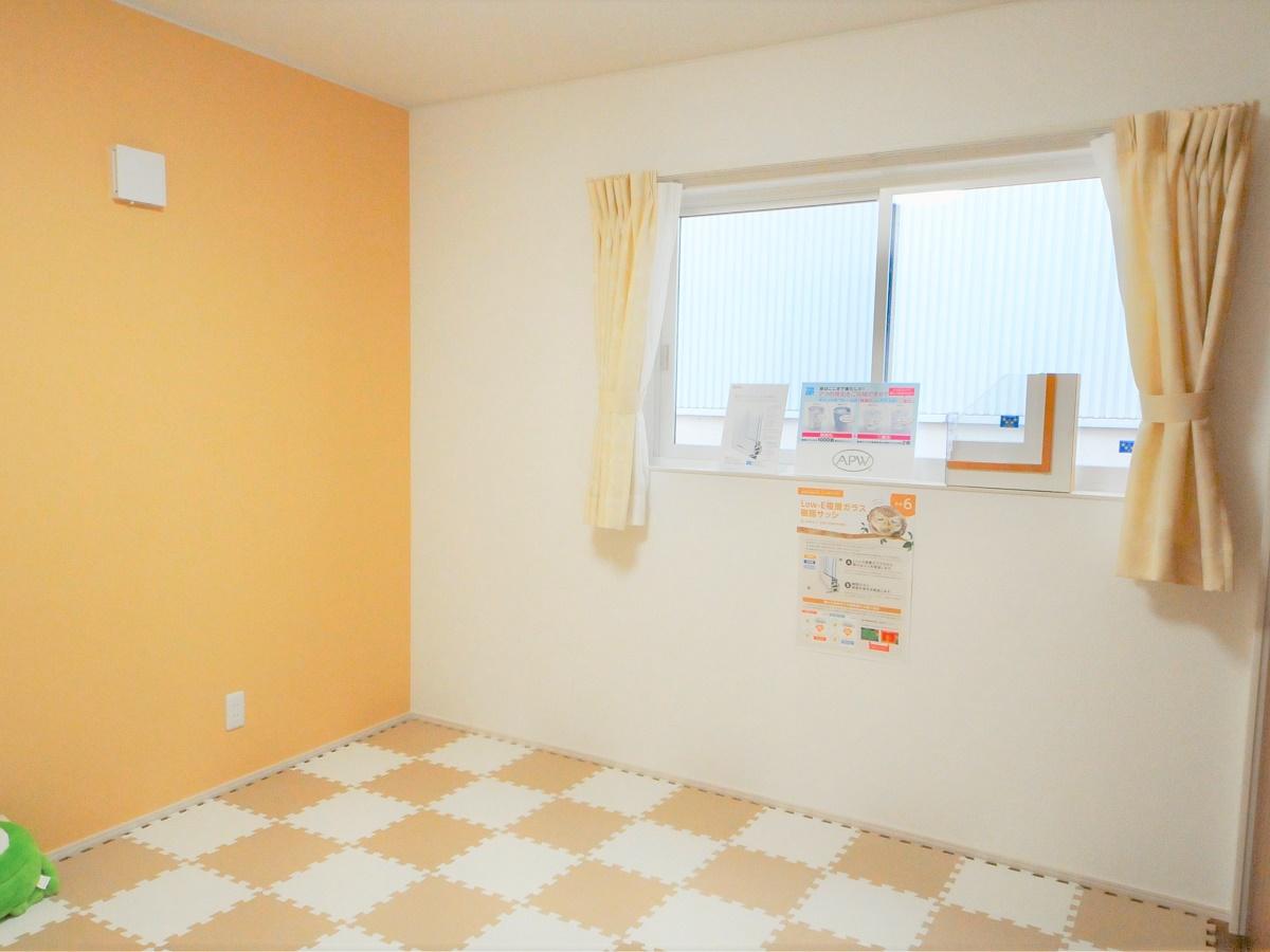 女の子向けの洋室はタイルカーペットを敷いている。淡いオレンジの壁は部屋をぱっと明るく見せるかわいらしい雰囲気。