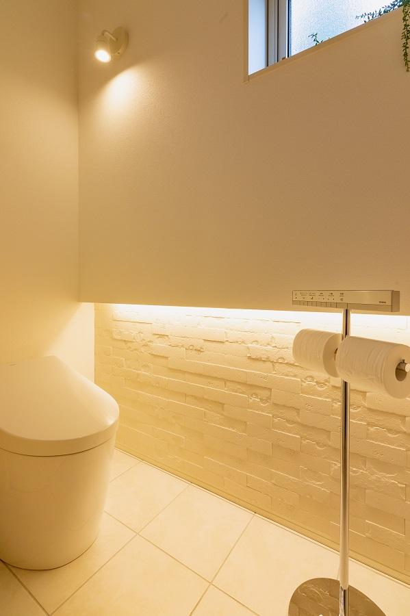 スポットライトや間接照明で柔らかい光の空間に。スタンドタイプのトイレットペーパーホルダーでスッキリと。