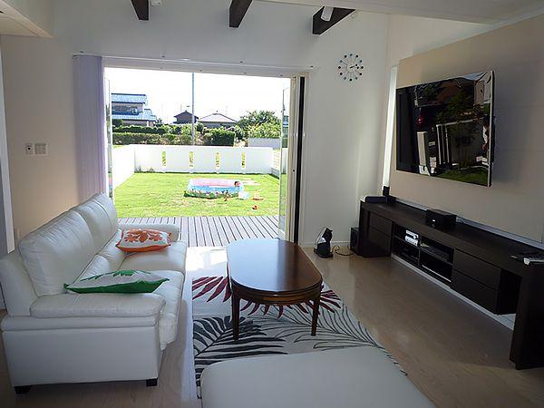 ハワイをイメージした家具がコーディネートされており、フルオープンサッシを採用。室内側とウッドデッキの段差をなくし、外と中との一体感を高めた開放的なリビングです。
