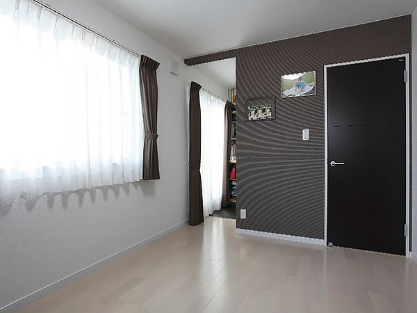 落ち着きのあるモダンな装いでまとめた寝室にはご主人の書斎スペース。(写真奥)を併設しました。