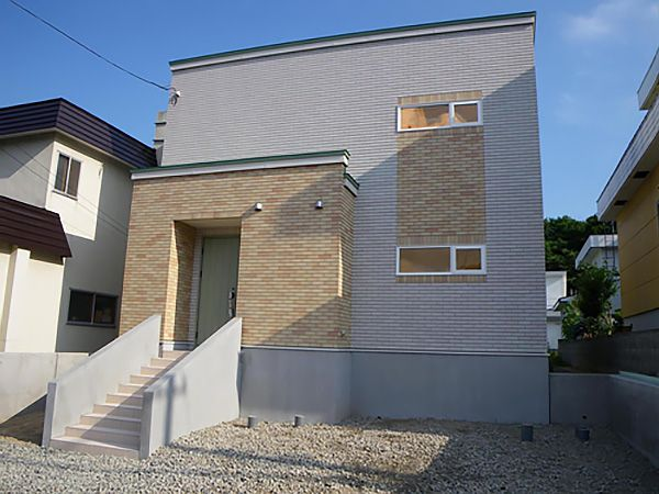 外観はナチュラルでありながら、タイルで飾った玄関ポーチとミストグリーンのドアでワンポイント加えています。