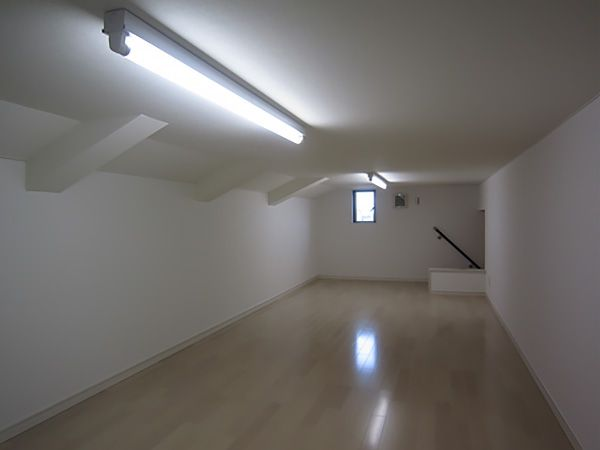 ウォークインクローゼットからダークブラウン色の階段を登り、大型のモノ収納部屋を配置しました。