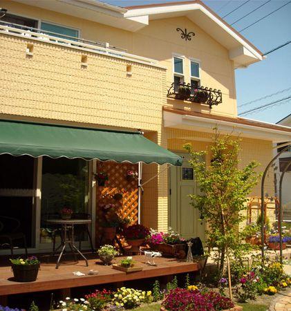 アイアンの壁飾りとフラワーBOXで、可愛らしい外観を演出しました。緑色の玄関ドアもお気に入りです。