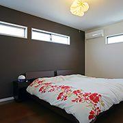 寝室の壁は濃淡色を織り交ぜ高級感を演出。大きな窓は設けず、空間デザインにこだわりました。