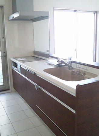 木目調のデザインが空間を引き立たせます。キッチン上に収納ボックスはなく、開放的な空間になっています。床は、メンテナンスのしやすいタイルを採用しました。