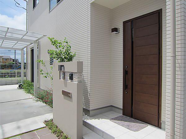 ホワイト系の外壁色にアクセントとなるナチュラルな玄関ドア。また建物の雰囲気を活かした外構のバランスが絶妙です。