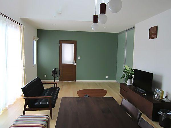 グリーンカラーのクロスにリビングドアがとても映えます。また、ソファやダイニングテーブルなどの家具にもこだわりを感じます。