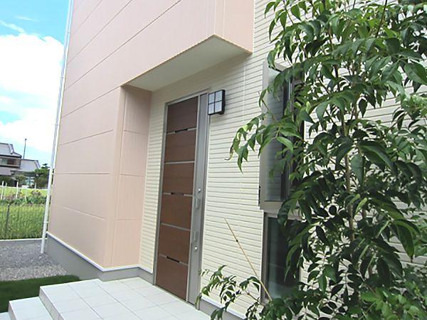 やわらかな外壁カラーが、玄関に植えた緑にもよく馴染みます。また、玄関上の2階部分を少し大きくすることによって、庇の役割もしてくれます。