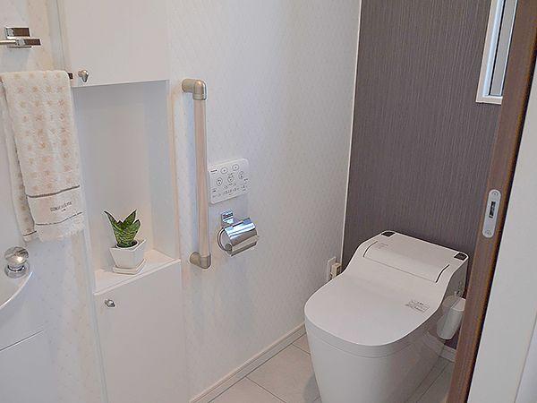 家族以外の方も使用することを意識したトイレ。スタイリッシュな泡洗浄機能付の便器、手洗器、ワンポイントのデザイン壁が、使う人への心遣いを表現します。