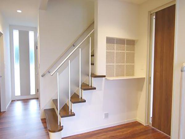玄関を開けると空間の広がりを考えて設計された階段が配置されています。正面の飾り棚もポイントです。