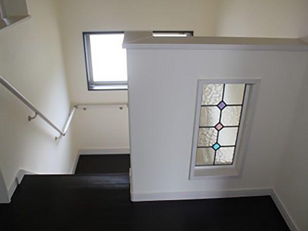 階段を登ったところの腰壁にステンドグラスを採用しました。日中は階段の窓からの光で綺麗に輝き、夜は階段照明の優しい光に照らされてロマンチックな感じになります。