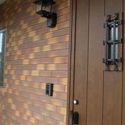 茶系の重厚感ある外壁に合わせて採用した木調の玄関ドアは、家全体の雰囲気によく馴染みます。