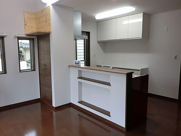 対面式のオークンキッチンの腰壁には壁埋め込みの収納を設置。
