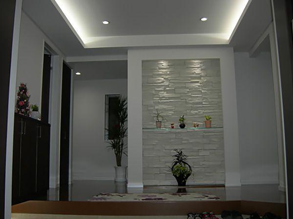 玄関ホール正面の装飾がエレガントさを演出し、天井のコーブ照明が空間の広がりを感じさせます。