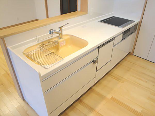 白く清潔感のあるキッチンにマンゴー色のシンクで彩りをプラス