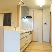白く清潔感のあるキッチンにマンゴー色のシンクで彩りをプラス。