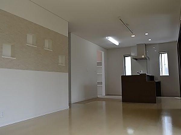 リビングスペースには壁面を利用し、ご家族のお写真などを飾るスペースとしてニッチを設計。キッチンの向は和室となっており、3枚の引き戸で空間を仕切れるようになっています。