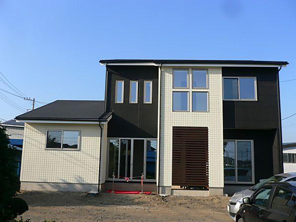 白と黒のシンプルモダンの外観。玄関前に格子をつけ、通りから目立たないように設定。屋根形状は太陽光発電システムを搭載するので、段付切妻にしてあります。