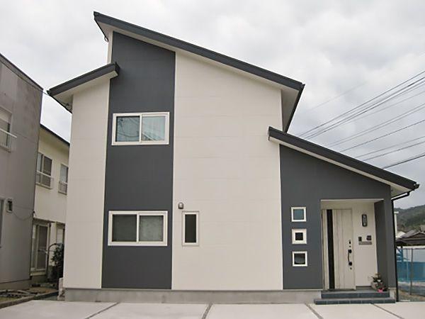 グレーとホワイトの2色を使用しモノトーンに。グレーのストライプがアクセントになっています。 片流れの屋根には、太陽光も載っています。 玄関扉も特徴的です。