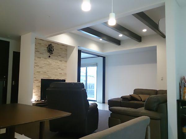 梁見せ天井で空間の広がりを持たせています。TVボードの後ろには石目調のクロスを使用し、リビング全体にアクセントを加えています。