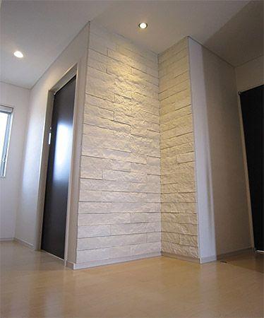 玄関ドア開けて正面には白い石を貼りました。玄関先がとても豪華にみえます。またこの石の為にダウンライトも設けました。白い石と、ダーク色の建具がとてもマッチしています。