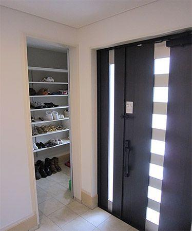玄関に下駄箱を置きたくないという希望を叶える為に考えたのが大型のクローク。たくさんの靴が収納可能でクローク内は泥汚れなどでクロスが汚れてしまっても分かりづらいように薄めのグレーのクロスを貼りました。またクローク内には鏡を設けお出かけの時には頭から足元まで確認してお出かけが可能です。