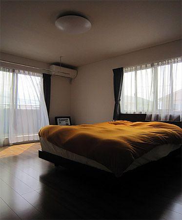 約10帖くらいある広い寝室、寝室には大きなウォークインクローゼットも併設。寝室の南側にはバルコニーがあるので、洗濯物が干しやすい&取り込みやすいようにホスクリーンも天井に設置しました。また室内は落ち着いた雰囲気を出すために一面だけにベージュのクロスをポイントに使いました。