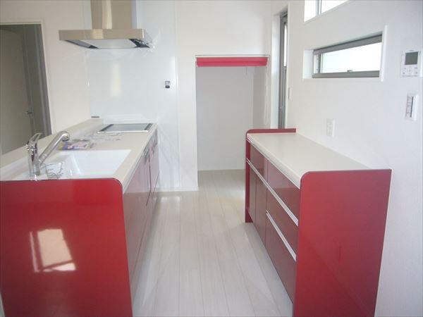 赤いキッチンの横には階段下を利用したパントリーがあるので収納もたくさん可能です。赤いロールルスクリーンもいい感じです。