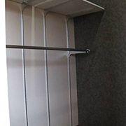 写真は2階洋室のウオークインクローゼット。高さや位置を変えるのもパーツを追加するのも、簡単に出来て安価な商業施設用スリット柱システム。ハンガーパイプと木棚板セットは各収納庫共通寸法で使いやすくしています。