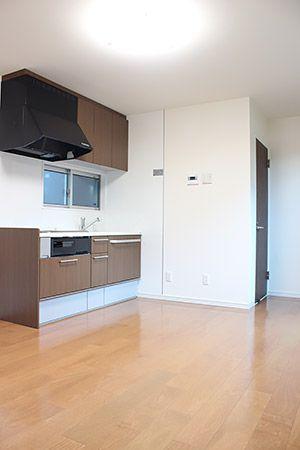 共有スペースを取らないように、キッチンはコンパクトな物を。建具に合わせて、シックな色調となっています。