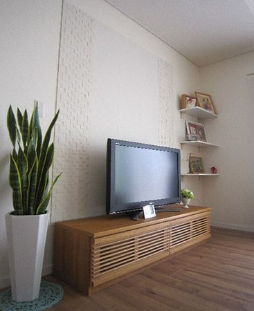 TVボードの後ろは玄関のニッチ同様、ご主人が貼られたデザイン壁材とご主人が作られた飾り棚が。デザイン壁在がとっても栄えます。また棚にはご家族の写真が飾られていてとっても良い雰囲気です。