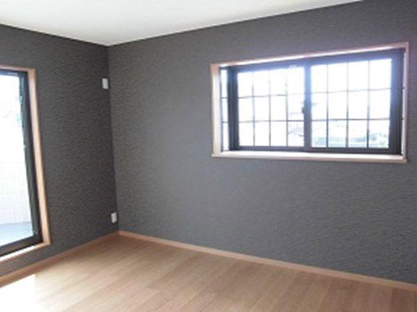 「落ち着いた雰囲気にしたかった」という寝室は、2面をダークな色のクロスにしました。
