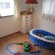 まだまだ一人で使うことのない子供部屋は子供さんのおもちゃがたくさん。レースのカーテンのアップリケは子供さんの要望により奥様がつけたとのこと。