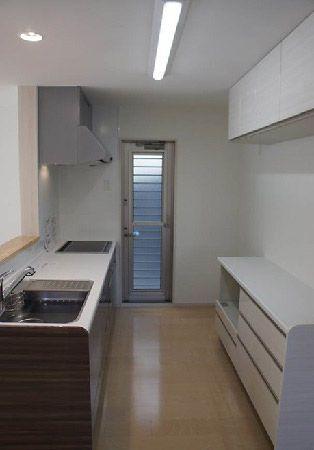 キッチンは木目が素敵なデザインを採用。吊戸を背面に設置し、カップボードも作り付けの物を採用し、収納力抜群のキッチンスペースになりました。