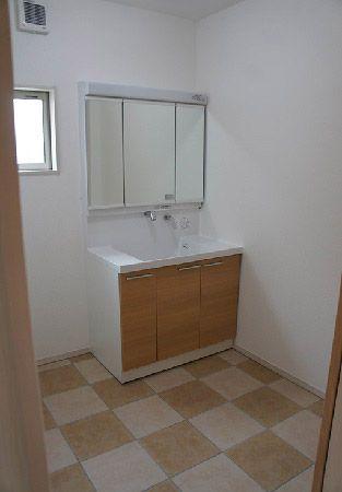 洗面は床暖房の為、床はタイル貼り。タイルは淡いベージュと濃いベージュの二色を採用。