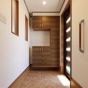 採光窓のついた玄関ドア、ダイニングスペースとの間に設置された窓により玄関スペースは明るさいっぱい