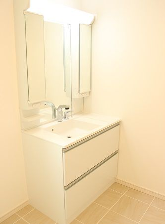 洗面台は白に統一し、洗濯物が干しやすいように、天井には収納式洗濯物干しを設置いたしました。