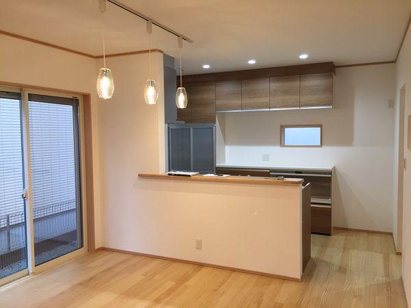 キッチンには木目調の扉を、床材には無垢材を使用し、やさしい風合いのLDKに